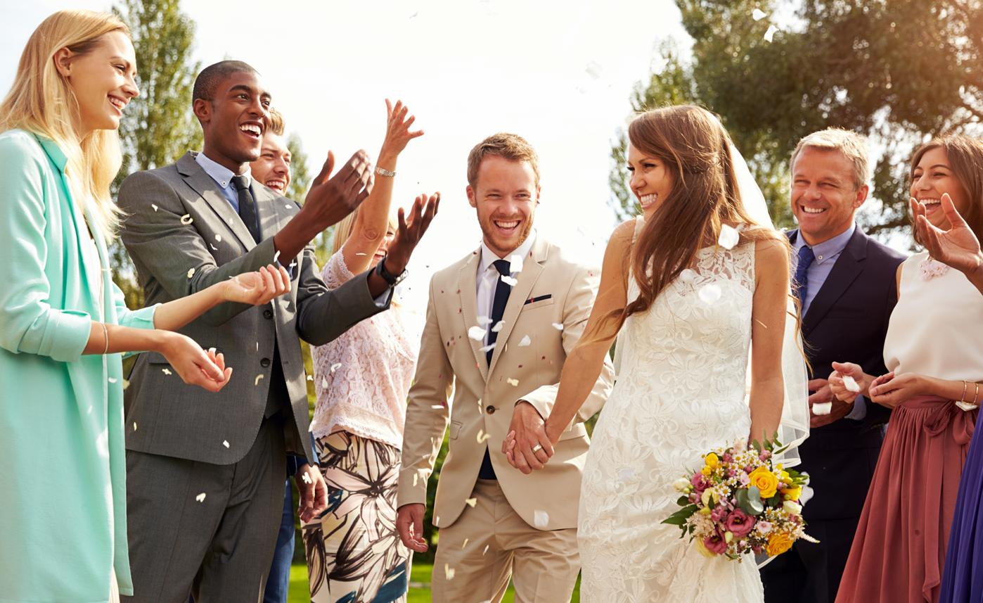 A newly married couple celebrate with their friends and family at their wedding.