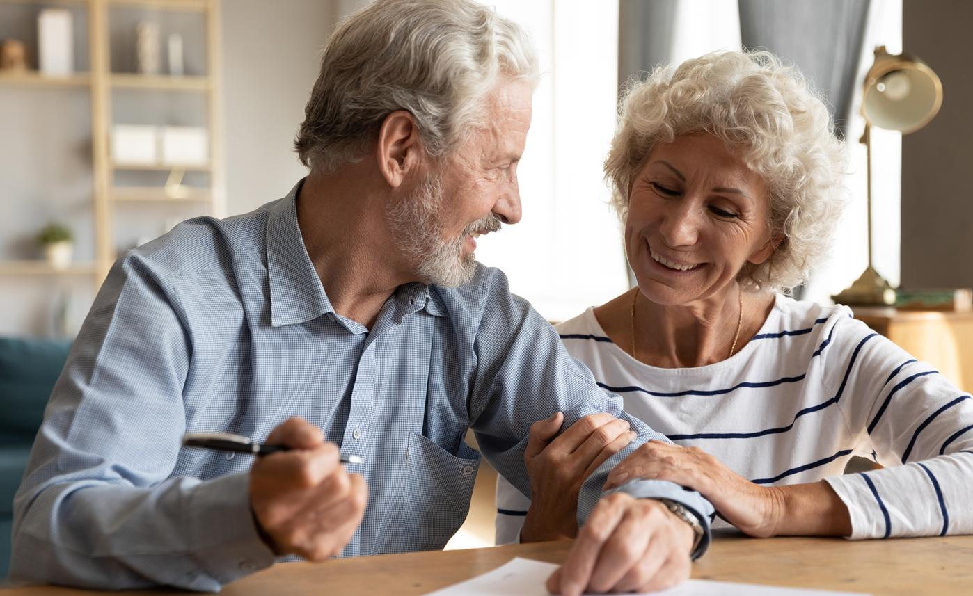 A retirement-age couple smiles at each other as the man signs a document on their kitchen table.