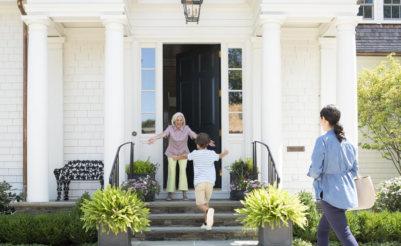 A young child runs up the front steps of a large house to greet his grandmother as his mom watches and smiles.