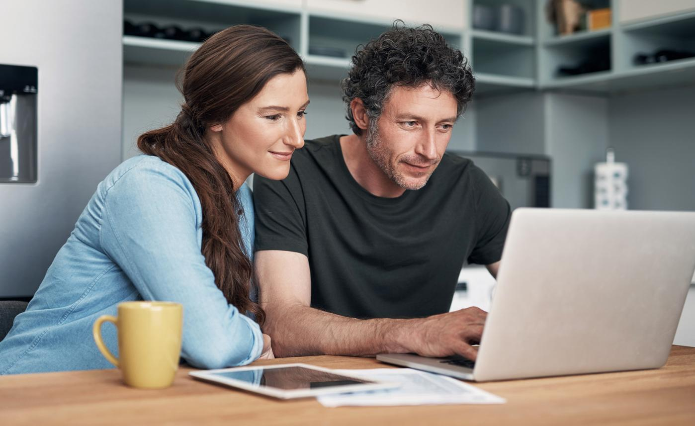 A couple sits at their kitchen table and reads about financial terms on their laptop.