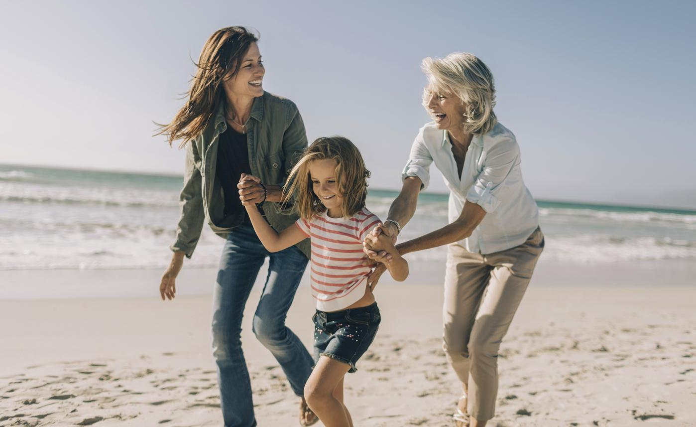 A retirement-aged woman laughs on the beach with her adult daughter and young granddaughter.