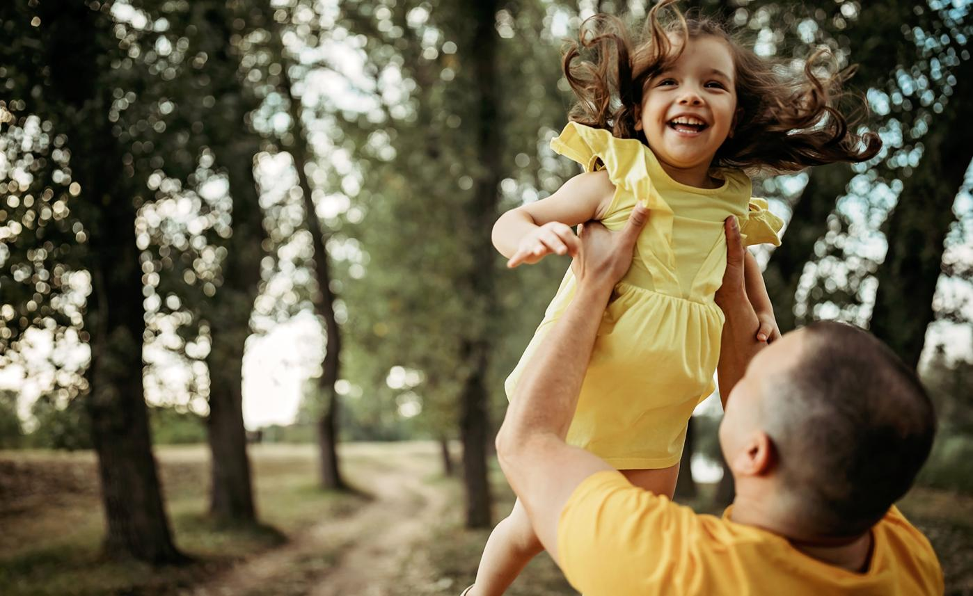 A father holds up his young daughter in a park as they laugh together.