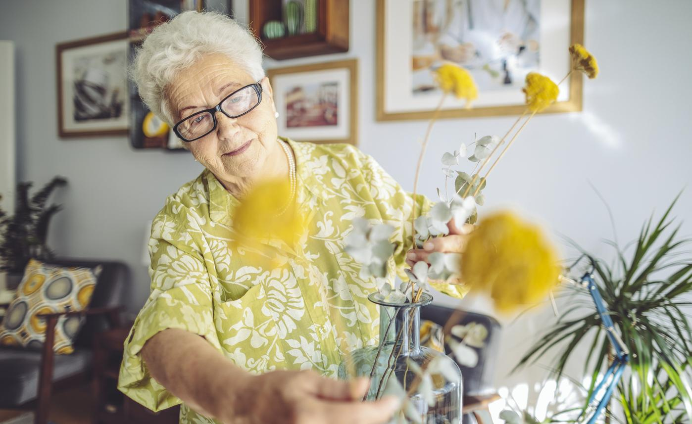 A retirement-aged woman puts together a flower arrangement in her home.