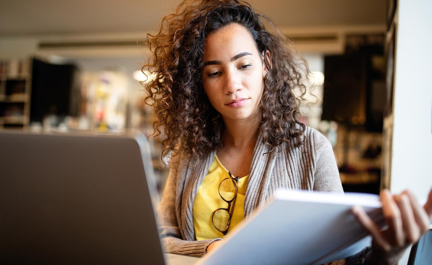 A young woman reviews a list of financial questions and looks up the answers on her laptop.
