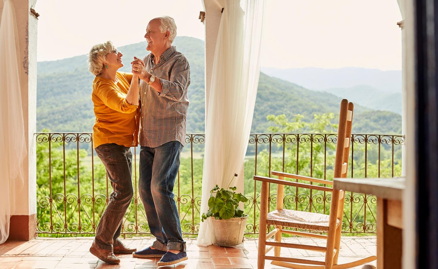 A retirement-aged couple dances together on a porch with a view of mountains.