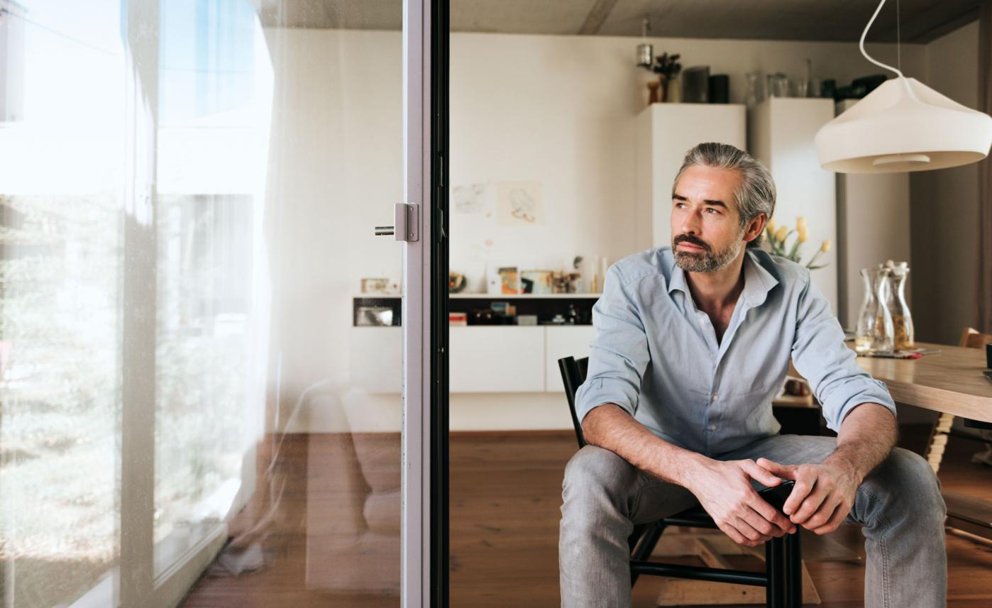 Man sitting in dining chair looking out window