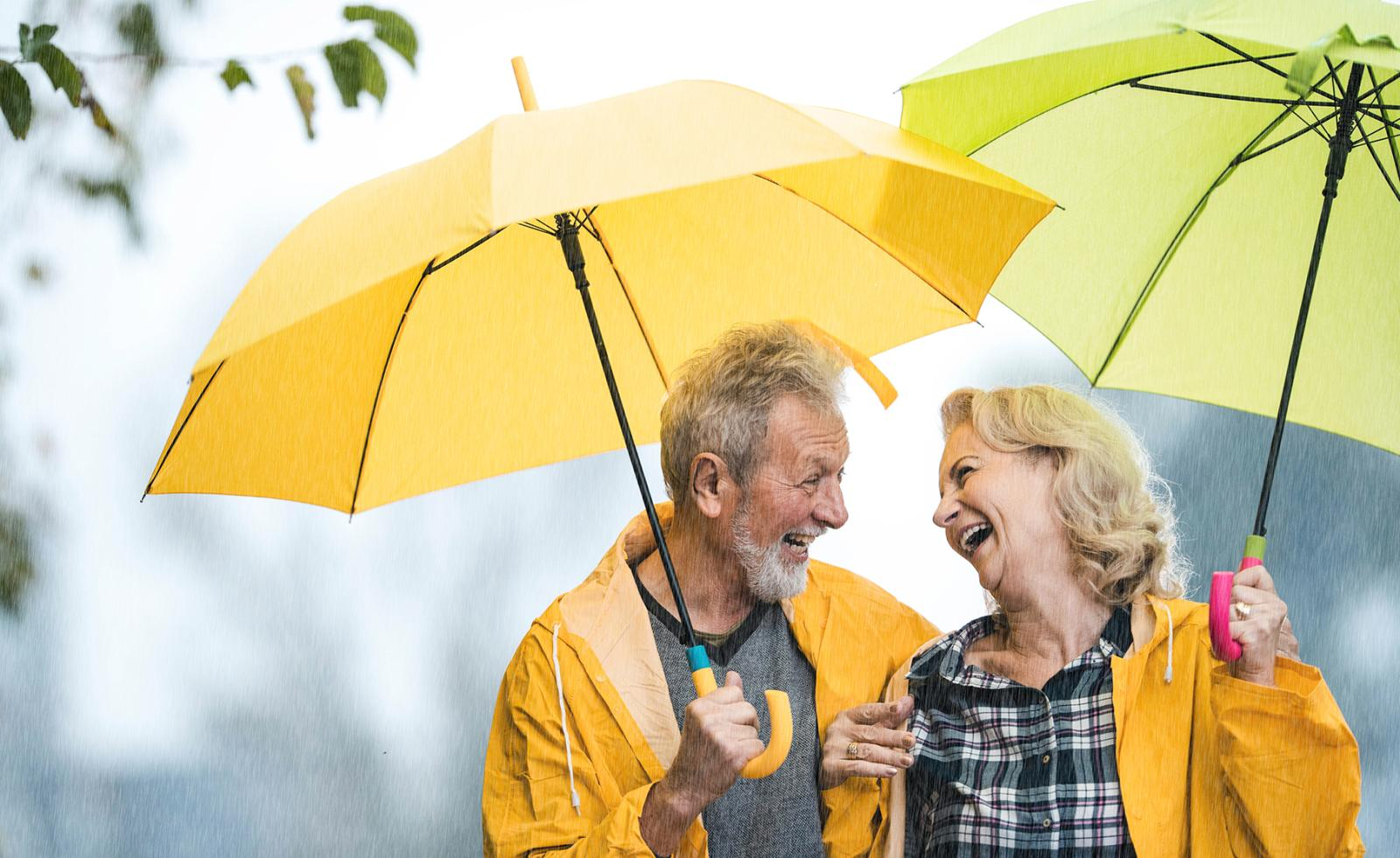 A senior couple laughs in the rain, with umbrellas and bright yellow raincoats, and enjoy the moment.