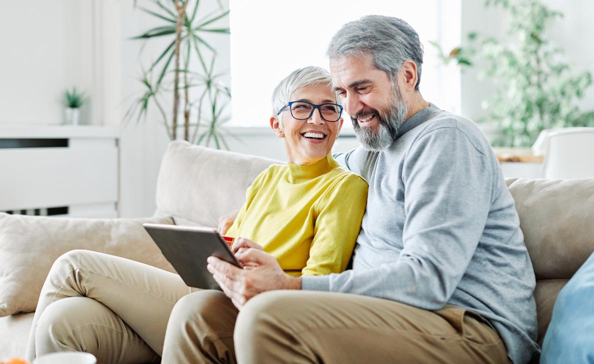 A retirement-age couple smiles as they read from a tablet on the couch.