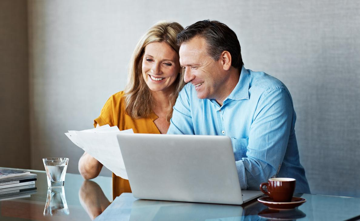 A middle-aged couple smiles as they review printed tax documents in front of their laptop.