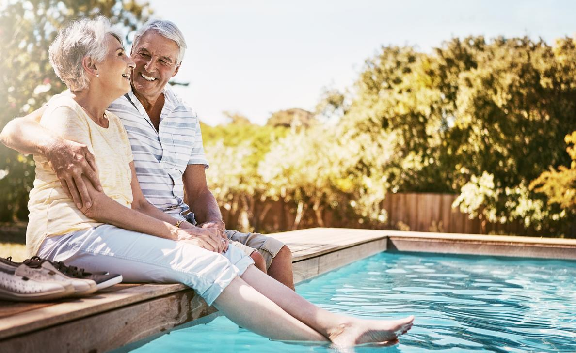 A retirement-aged couple smile together as they dip their feet in their pool on a sunny day.