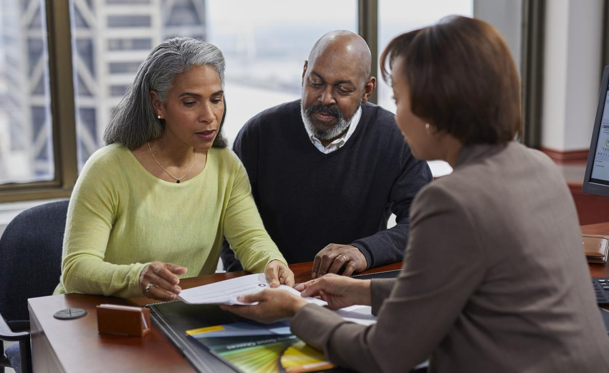 An Edward Jones advisor consults two clients on their financial options.