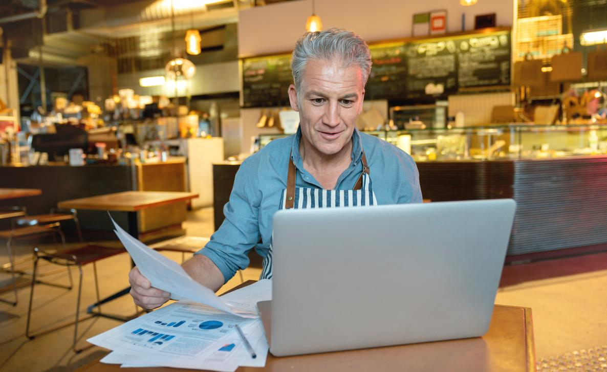 A man looks at printed financial documents and reads from his laptop in the small cafe that he owns.