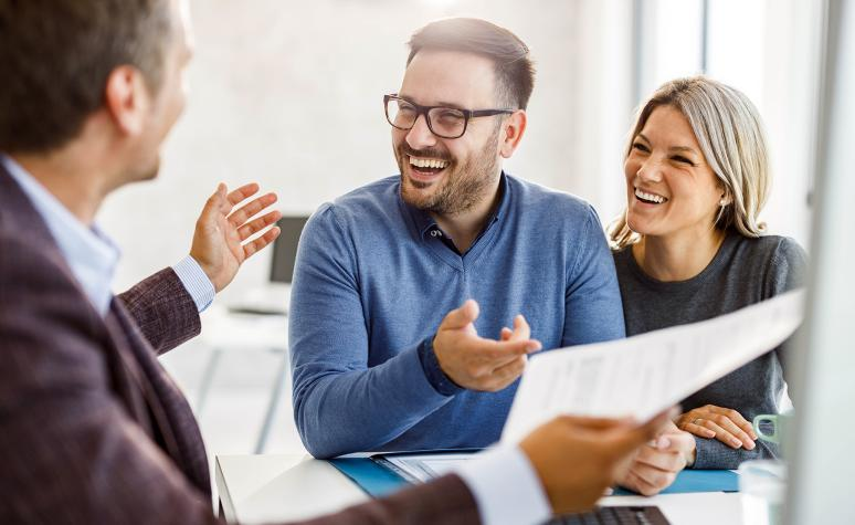A financial advisor laughs with two clients at his office.