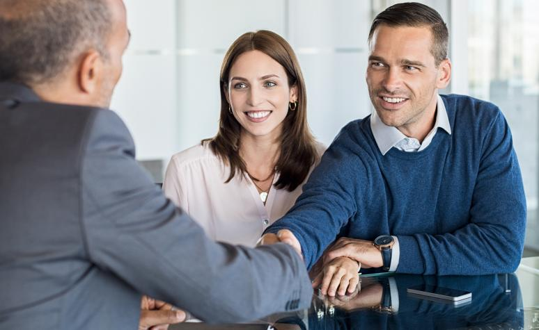 A couple shakes the hand of their financial advisor in a branch office.