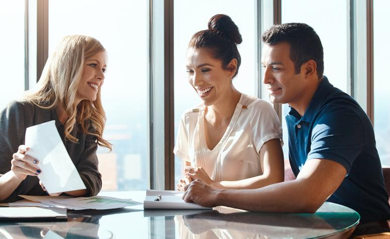 Two clients sit with their Edward Jones advisor in her office and discuss information on a document.